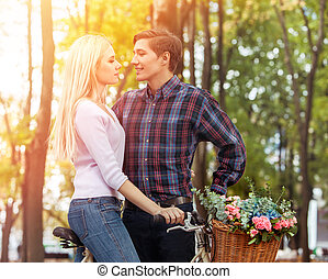 Love couple kiss on bicycle and spring flower basket park.