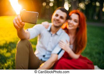 Love couple makes selfie in summer park on sunset