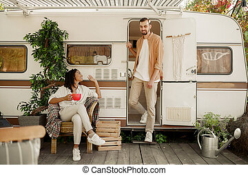 Love couple relaxing in rv, camping in a trailer