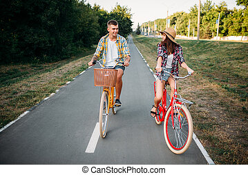 Love couple riding on retro bikes in summer park