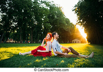 Love couple sits on grass in park, romantic date