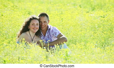 Love couple sitting in flowers
