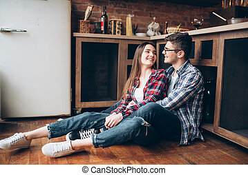 Love couple sitting on the kitchen floor and hugs