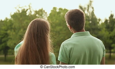 Love couple standing in a park and talking