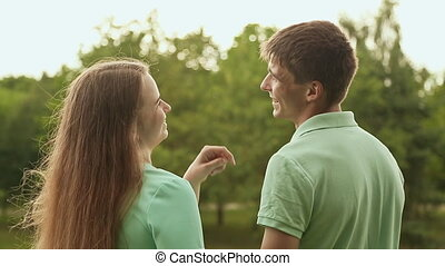 Love couple standing in a park and talking. View from the back.