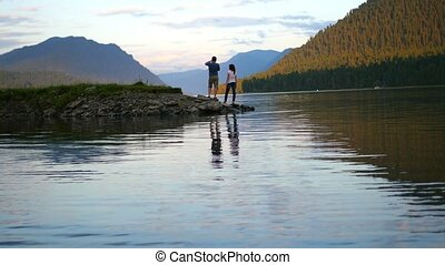 love couple walking on river at sunset