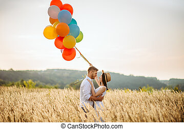 Love couple with colorful balloons in a rye field