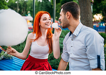 Love couple with cotton candy in summer park