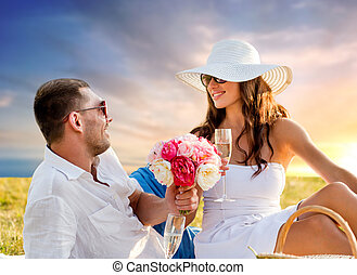 couple with flowers drinking champagne at picnic