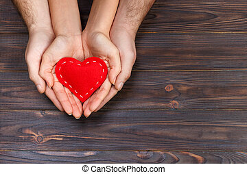 Love, family concept. Close up of man and woman hands holding red rubber heart together