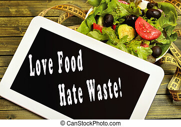 Love food Hate waste written on digital tablet