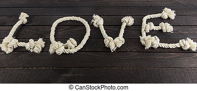 Love form with rope on wooden background.
