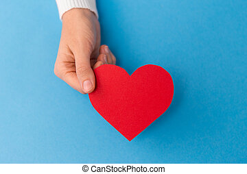 hand holding red heart shape on blue background