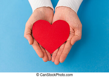 hands holding red heart shape on blue background