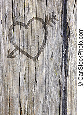 Love heart and arrow graffiti carved into wood