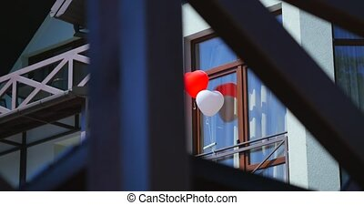 Love heart balloons on house background