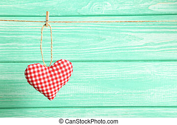 Love heart hanging on rope on a mint wooden background