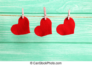 Love hearts hanging on rope on a mint wooden background