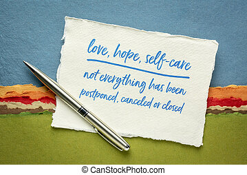 love, hope, self-care are - not everything has been postponed, canceled or closed, handwriting on white Khadi rag paper against colorful abstract landscape, positivity and optimism during coronavirus, covid-19 pandemic