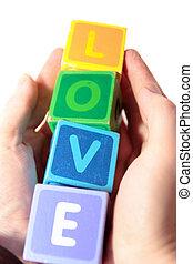 love in wooden play blocks letters held in hands