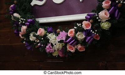 Love inscription on a wooden background, flashing lights and flowers. Decorative artistic animation devoted to the Valentines day or wedding.