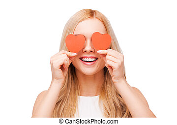 Love is a great feeling! Beautiful young blond hair woman holding heart shaped valentine cards in front of her eyes and smiling while standing isolated on white