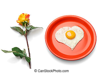 Heart shaped egg on the red plate next to fresh rose.