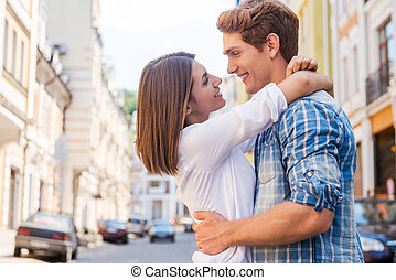 Love is in the air. Beautiful young loving couple hugging and looking at each other while standing outdoors