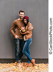 Love is in the air. Full length of beautiful young couple bonding to each other and smiling while leaning at the grey wall with fallen leaves laying around them
