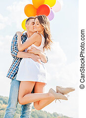 Love is in the air. Man holding a beautiful young woman and balloons while kissing her