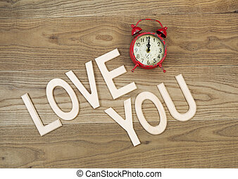 Overhead view of an old table top alarm clock and large wooden letters spelling out Love You on rustic wood