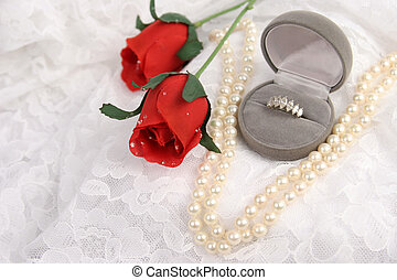 a diamond ring, string of pearls, and silk roses on lace - room for text