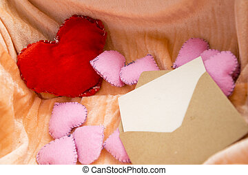 Love letter for Valentines Day concept. Craft envelope with card in box full of hearts toys.