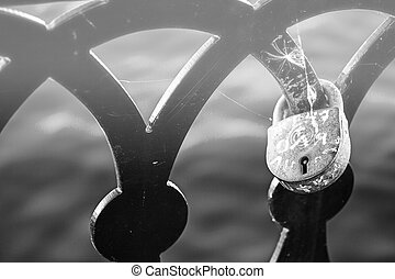 Love lock on the railing of the old bridge close up