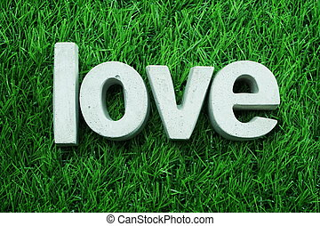 Love made from concrete alphabet top view on green grass