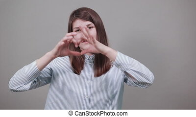 Love message heart shaped hand gesture. Valentines day card. Young attractive woman, dressed blue shirt with brown eyes, brunette hair, grey background