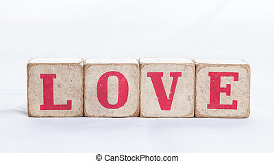 Love message written in wooden blocks on white background.