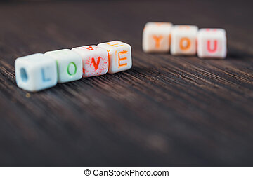 Love message written in wooden blocks on wooden background