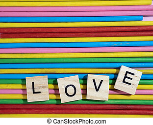 Love message written in wooden blocks placed on colourful wood sticks