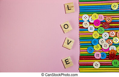 Love message written in wooden blocks placed on pink background