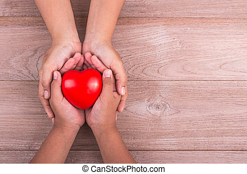 Love Mom Concept : Woman holds her young kids hands supporting red heart on brown wooden table. Free space for text of Mother's Day celebration.