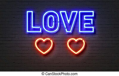 Love neon sign on brick wall background.
