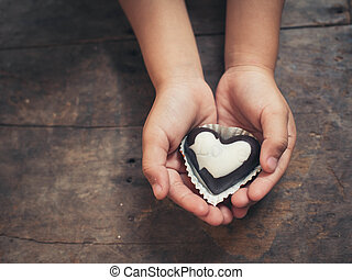 Love note on black and white chocolate in kid's hand