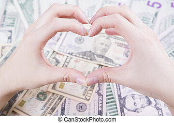 Love of money concept. Hands on dollars background.