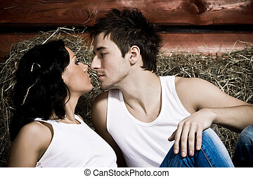 Love on a mow - Beautiful young couple on hayloft