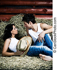 Love on a mow - Young beautiful couple on hayloft