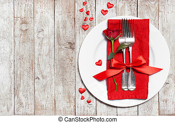Love or valentine's day concept with vintage cutlery, red roses and hearts on a wooden background. Top view with copy space