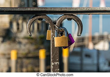 Love padlocks on a railing in the harbor on blurred lighthouse b