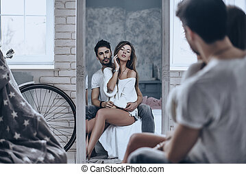 Love reflection. Rear view of beautiful woman looking at her reflection in the mirror while sitting in her boyfriends arms
