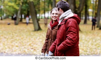 happy young couple walking in autumn park